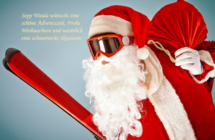 Santa Claus with red sack and ski equipment
